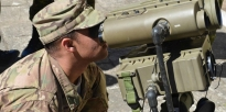 Soldier using the optics on the Lightweight Laser Designator Range Finder.