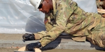 Soldier smooths a wet concrete surface .