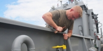 Soldier prepares a fuel supply line aboard the U.S. Army Landing Craft Utility 2031.