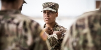 Warrant Officer reads through his checklist during a preflight inspection of an apache helicopter